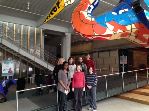 A group of smiling Bagels & Bytes attendees standing under the colorful oversized Crane (water bird) in the Children's Museum lobby.